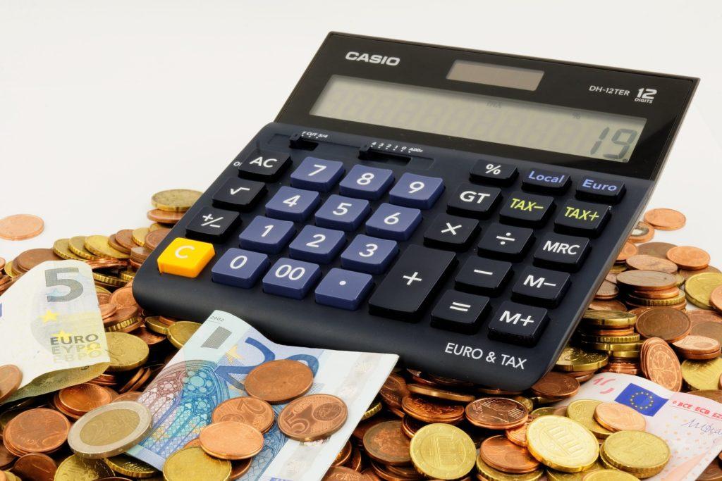 Op de afbeelding zie je een rekenmachine en munten en bankbiljetten